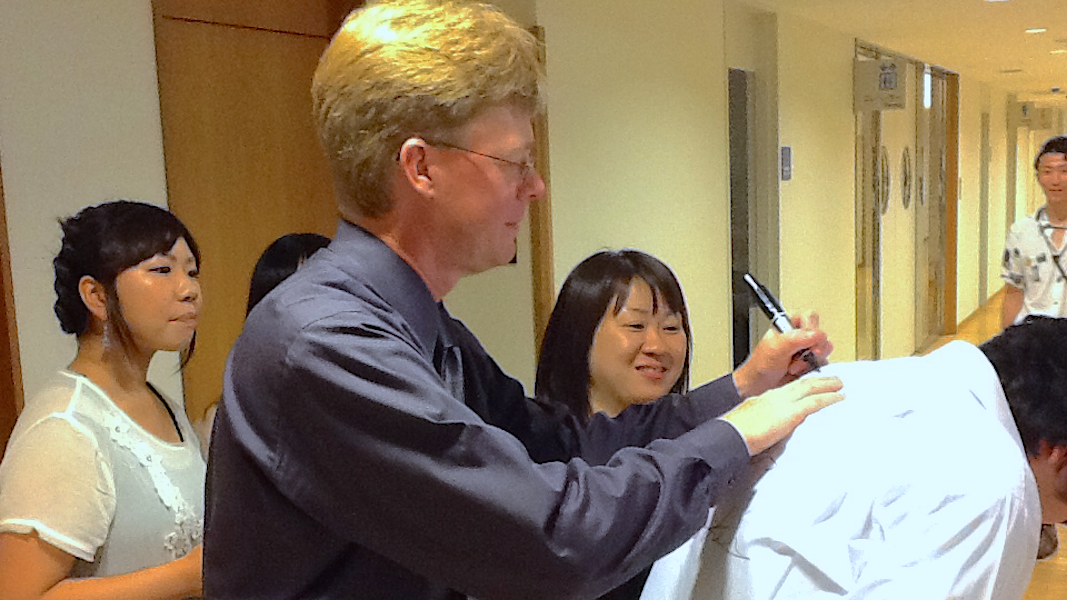 Autographing a shirt for a member of the Musashino Wind Ensemble